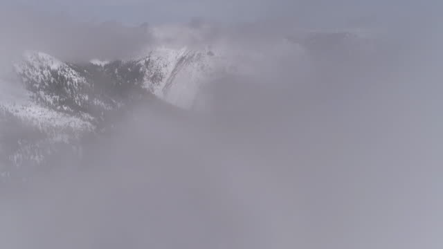 Aerial Flying Through Fog Clouds to Reveal Hazy Snow Covered Mountain Forest video