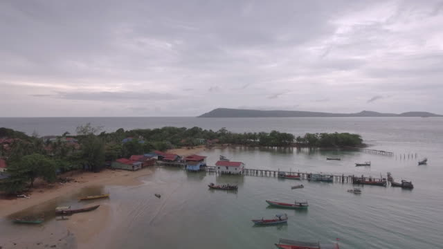 Aerial : flying towards fishing village and wooden pier on the sea bay video