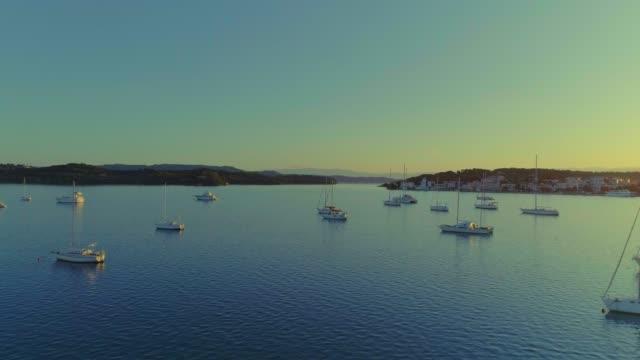 Aerial - flying upwards above a small harbor at dusk - Porto Heli - Porto Cheli - Greece - Argolis - Argolida video