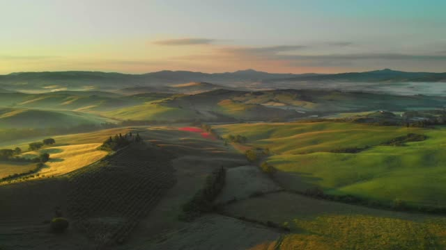 Aerial flyover the beautiful sunset landscape in Tuscany, Italy.
