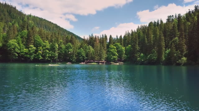 Aerial flythrough beautiful blue mountain lake against the backdrop of mountains and forests of spruce and pine trees video