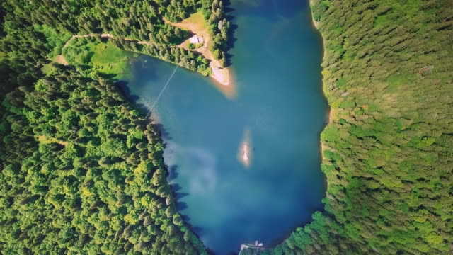 aerial flythrough of beautiful mountains and forest and rotate around the axis of an incredible blue lake - canada travel stock videos and b-roll footage