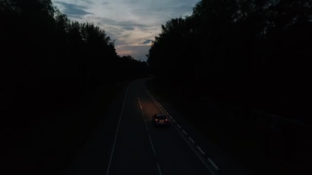 Aerial follow car rides on forest road at night