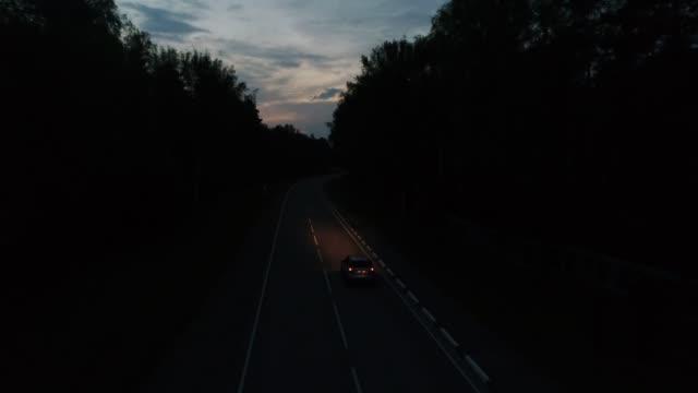 aereo seguire le corse in auto su strada forestale di notte - notte video stock e b–roll