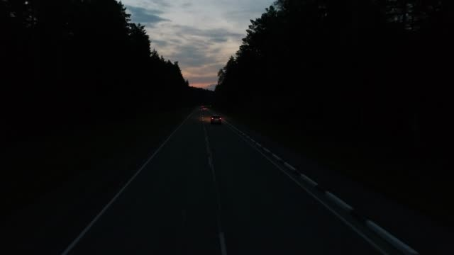 Aerial follow cars on the forest road at dawn