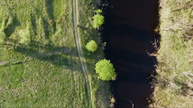 aerial follow of bicyclist bike or motorcycle riding unpaved gravel countryside road path near river top bird eye view on beautiful sunset - ghiaia video stock e b–roll