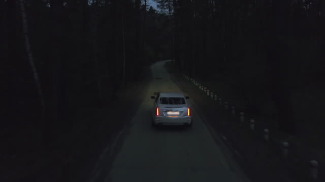 Aerial follow view white premium car Cadillac Cts driving on dark countryside road among summer forest at night. View from drone car with xenon headlights riding on night road through dark forest Aerial follow view white premium car Cadillac Cts driving on dark countryside road among summer forest at night. View from drone car with xenon headlights riding on night road through dark forest luxury car stock videos & royalty-free footage