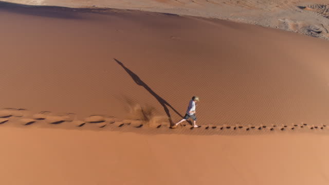 Aerial following shot of male tourist running down sand dunes in the Namib desert video