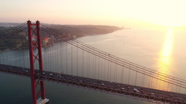 Aerial footage 25th April bridge in shining Aeria view suspension bridge over Tagus river in Lisbon. Drone flying above 25th april bridge symbol of Portugal in sun shining overlooking road with driving cars in bottom european culture stock videos & royalty-free footage
