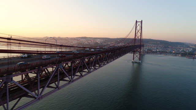 Aerial footage along 25th April bridge with driving cars Aeria view suspension bridge over Tagus river in Lisbon. Drone flying along 25th april bridge overlooking close up metall structure and driving cars in sun shining, beautiful landscape at sunset european culture stock videos & royalty-free footage