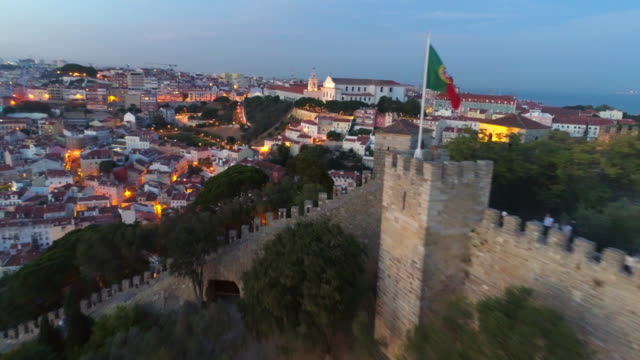 Aerial footage ancient fortress in Lisbon at sunset Aerial view medieval fortress on hill top in Lisbon. Drone flying near ancient wall of Castelo de Sao Jorge with flapping flags at night time and illuminated city streets portugal stock videos & royalty-free footage
