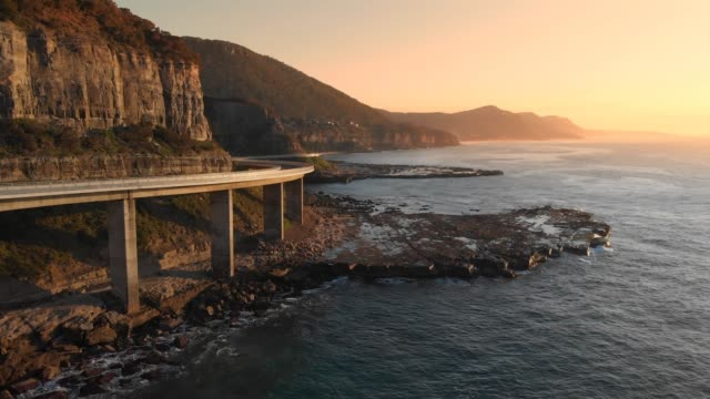 vídeos de stock e filmes b-roll de aerial footage australia sea cliff bridge coastal drive sunrise coastal seascape - sul