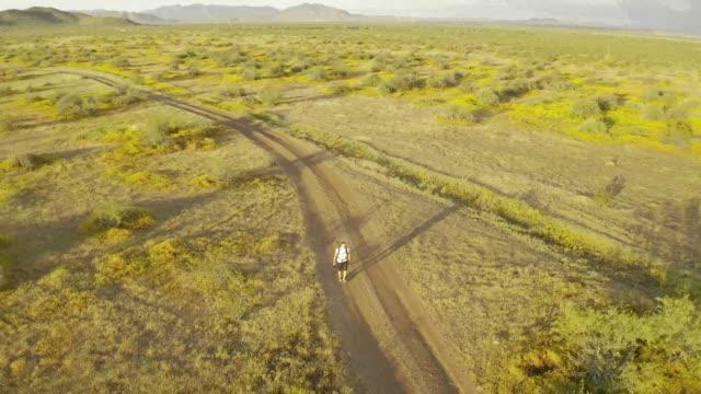 Aerial footage circling a man hiking through the Sonoran Desert of Arizona alone
