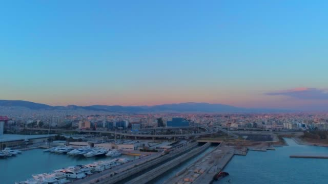 Aerial footage -  Drone - flying over a marina and into a traffic hub in south Athens, Faliro, Greece at sunset video