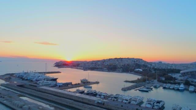 vídeos de stock, filmes e b-roll de imagens aéreas - zangão - voando sobre uma marina e um hub de tráfego no sul de atenas, ao pôr do sol de faliro, grécia - atenas grécia