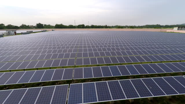Aerial footage flying backwards over solar panels in 4K video