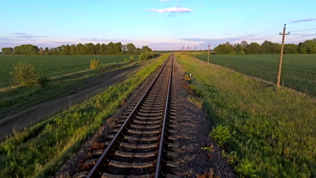aerial footage from a drone flying along a train track in a rural - vídeo