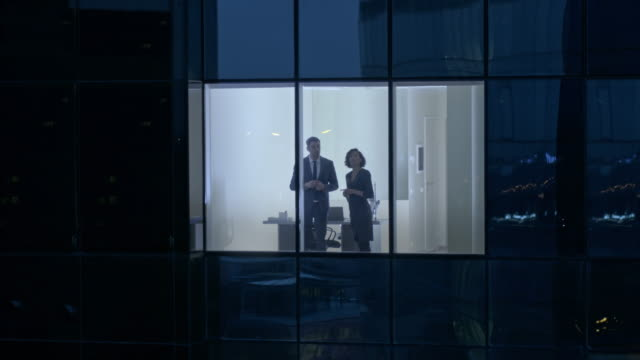 Aerial Footage From Outside of the Skyscraper: Businessman and Businesswoman Talking while Standing in the Office Window. Retrieving Flying Shot of the Business District in the Evening and Businesspeople Working in the Big City. video