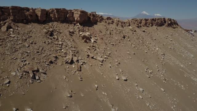 stockvideo's en b-roll-footage met luchtfoto beelden van de drone van de verbazingwekkende valle de la luna (moon valley) in atacama desert een geweldige plek voor de geologie en een ontzag reisbestemming. een volwassen persoon die kijkt naar het uitzicht - maasvallei