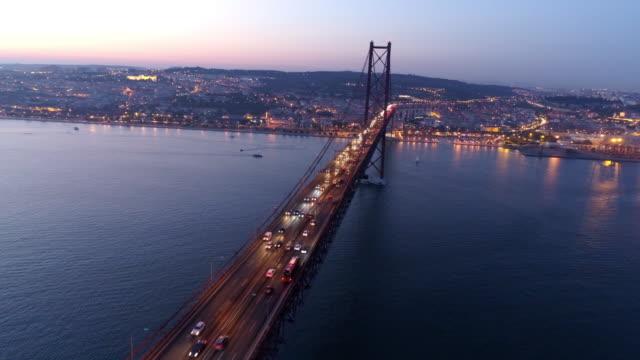 vídeos de stock e filmes b-roll de aerial footage illuminated 25th april bridge in twilight - portugal