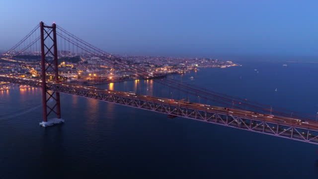 stockvideo's en b-roll-footage met luchtfoto beelden verlicht 25e april brug in twilight - portugal