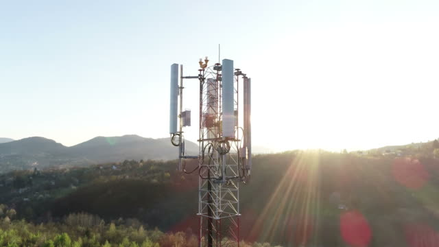 vidéos et rushes de images aériennes d'une antenne 3g 4g, le tir tourne autour d'elle, avec des fusées éclairantes de lentille - transmission