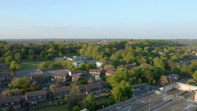 Aerial footage of a generic small English town during sunset in Summer