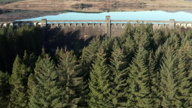 Aerial footage of a Scottish loch with a hydro electric dam surrounded by hills and an area of forest Drone footage of a man made fresh water loch in a remote location of Dumfries and Galloway, south west Scotland. The dam was created during the construction of the Galloway hydro electric scheme and was built during the 1930s. The video was captured on a bright winter morning with no wind which gave the loch a very clam surface. galloway scotland stock videos & royalty-free footage