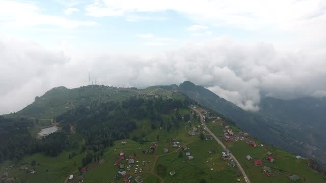 Aerial footage of a village hidden behind fog.