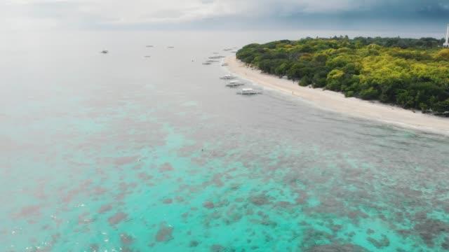aerial bilder av balicasag island i filippinerna. fantastisk utsikt över korall rev och circle island. panglao, bohol, vit strand, palmer, båtar/4k drone video - antenn telekommunikationsutrustning bildbanksvideor och videomaterial från bakom kulisserna