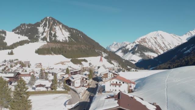 aerial footage of berwang austria in winter, ski village, bright sunlight hitting the slopes - stato federato del tirolo video stock e b–roll
