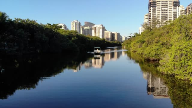 Aerial footage of boat in Marapendi canal in Barra da Tijuca on a summer day, with a boat slowly traveling along river. Tall residential skyscrapers on both sides, with green vegetation video