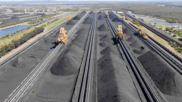 Aerial footage of coal stockpiles and bucket wheel excavators at export depot. Fossil fuel reliance, sustainability and global warming concepts.