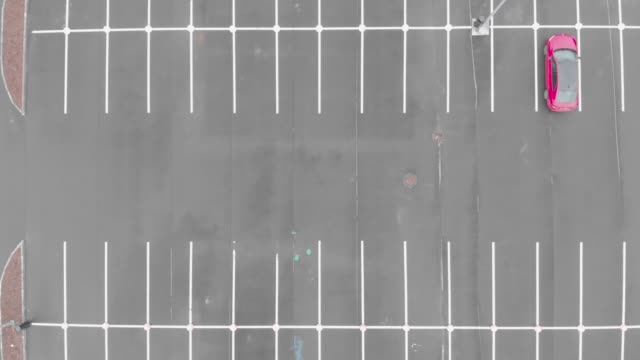 Aerial footage of empty parking lot with lonely red car