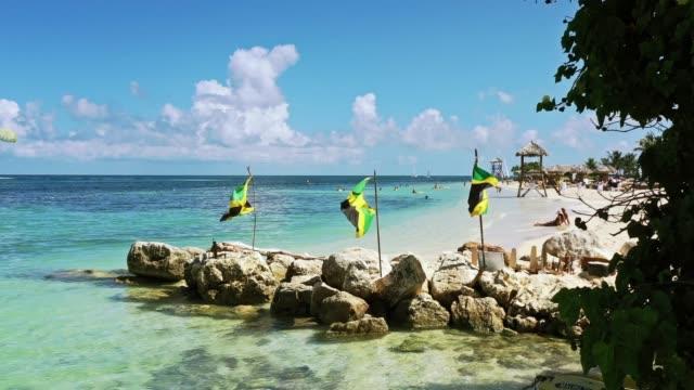 Luftaufnahmen von jamaikanischen Flaggen an einem wunderschönen tropischen Strand auf Jamaika – Video