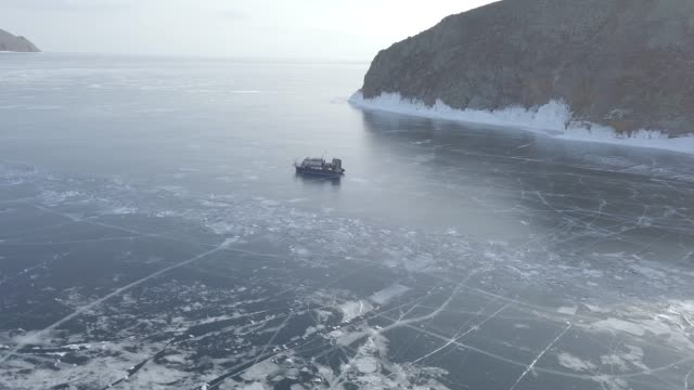 vídeos de stock e filmes b-roll de aerial footage of  khivus boats hovercraft ship boats on air cushion glides rides on frozen lake baikal to olkhon island. beautiful cracks patterns on ice snowy landscape. khuzhir, siberia, russia. drone flies around and above boats. - lago baikal