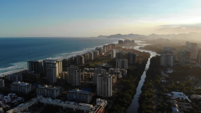 Aerial footage of Marapendi canal and Barra da Tijuca on a summer day, with the Barra and Recreio beach visible during sunset video