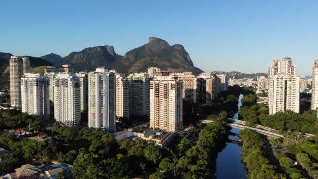 Aerial footage of Marapendi canal in Barra da Tijuca on a summer day, with slow rise to see Gavea Stone behind the tall residential skyscrapers video