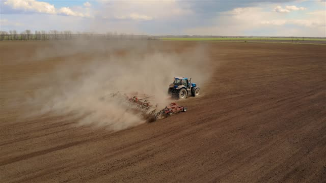Aerial footage of modern blue tractor with red plough plowing or cultivating large field Aerial footage of modern blue tractor with red plough plowing or cultivating large field. Spring agronomic activity on agricultural land harrow agricultural equipment stock videos & royalty-free footage
