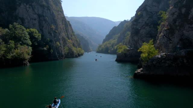 luftaufnahmen von menschen, die an einem sonnigen tag in der matka-schlucht in mazedonien kanu fahren - kanu stock-videos und b-roll-filmmaterial