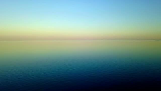 antenn material av lila solnedgången på vackra lugna vatten av havsytan i varm kväll twilight. kameran flyttas ovanför lugna havet på soluppgången med färgstark palett horisont skyline. koppla av koncept - pink sunrise bildbanksvideor och videomaterial från bakom kulisserna