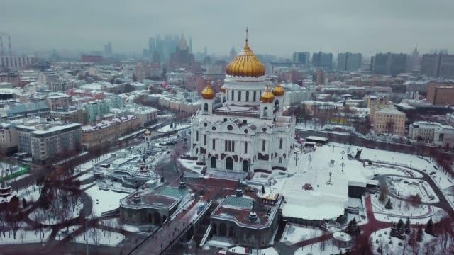 aerial bilder av ryska ortodoxa tempel kristus frälsaren i moskva på vintern. det snöar överallt. det finns sevärdheter, historiska byggnader, moscow city och stalins skyskrapor runt domkyrkan. - röda torget bildbanksvideor och videomaterial från bakom kulisserna