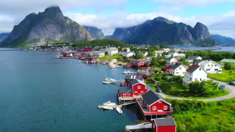 vídeos de stock e filmes b-roll de aerial footage of small fishing village of hamnoy on lofoten islands in norway, popular tourist destination with its typical red houses and natural beauty. aerial 4k ultra hd. - aldeia