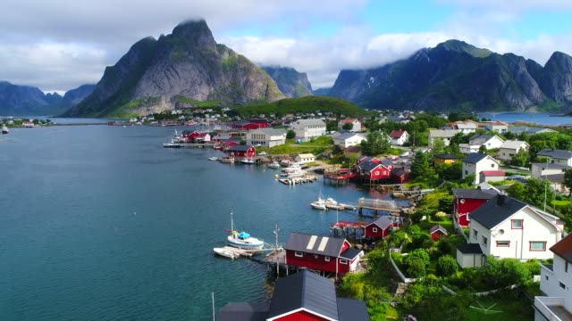 vídeos de stock e filmes b-roll de aerial footage of small fishing village of hamnoy on lofoten islands in norway, popular tourist destination with its typical red houses and natural beauty. aerial 4k ultra hd. - reine