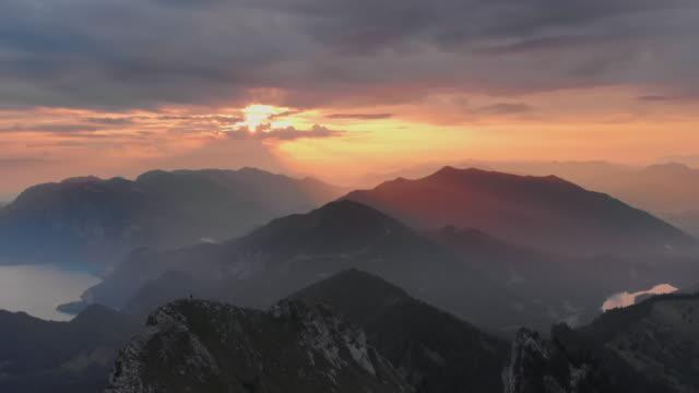 luftaufnahmen der spektakulären berglandschaft bei sonnenaufgang. ein wanderer klettert auf dem schafberg im salzkammergut - salzburg stock-videos und b-roll-filmmaterial