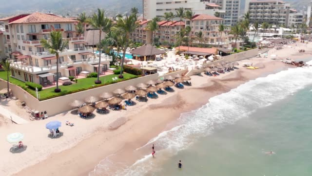 Aerial footage of the beautiful beach and town of Puerto Vallarta in Mexico, the town is on the Pacific coast in the state known as Jalisco, showing the beach and coastal front