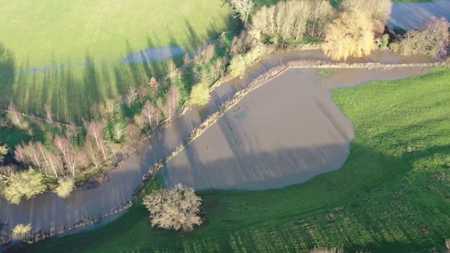 Aerial footage of the British country side fields in the winter time showing a river that has burst it's bank to overspill water on the fields, taken in the town of Wetherby in Yorkshire in the UK