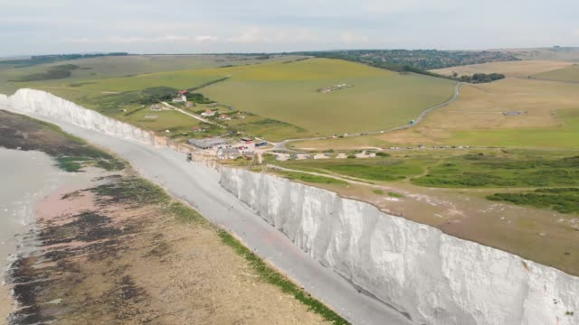 Aerial footage of the famous Seven Sisters chalk cliffs tops by the English Channel. They form part of the South Downs in East Sussex, between the towns of Seaford and Eastbourne in southern England,