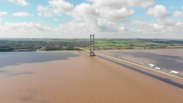 Aerial footage of The Humber Bridge, near Kingston upon Hull, East Riding of Yorkshire, England, single-span road suspension bridge, taken on a sunny with traffic traveling on the road.