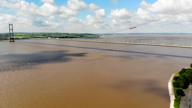 aerial bilder av humber bridge, nära kingston upon hull, east ridning i yorkshire, england, single-span road hängbro, tas på en solig med trafik som färdas på vägen. - skrov bildbanksvideor och videomaterial från bakom kulisserna